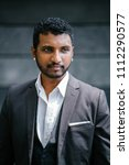 Small photo of Portrait of a handsome, roguish young Indian man in a 3-piece suit, white shirt and pocket square.