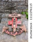 Small photo of Fort William, Scotland - June 11, 2012: Pink wood anchor laid at war memorial on The Parade square shows slogan Sure and Stedfast. Gray stones as background.