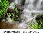 small waterfall in the garden. | Shutterstock . vector #1112349917