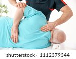 young physiotherapist working... | Shutterstock . vector #1112379344