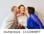 parents kiss their smiling... | Shutterstock . vector #1112384897