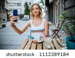 young woman sitting in cafe and ... | Shutterstock . vector #1112389184