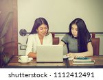 two young women sit at the desk.... | Shutterstock . vector #1112412491