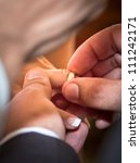 Groom putting wedding ring on bride finger - stock photo
