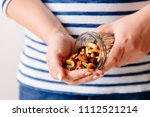 hands holding a jar of nuts and ... | Shutterstock . vector #1112521214