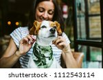 Stock photo young beautiful woman having great time with her little sweet dog in a restaurant after their meal 1112543114