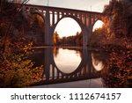 Bridge Reflecting In River At...