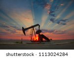 Oil well, pump jack, in the San Joaquin Valley of Central California at sunset. Oil industry background.