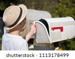 school boy opening a post box... | Shutterstock . vector #1113178499