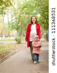 Happy pregnant mother with baby in autumn park - stock photo