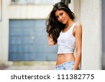 Portrait of a beautiful woman smiling in urban background - stock photo