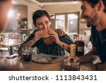 young woman eating burger while ... | Shutterstock . vector #1113843431