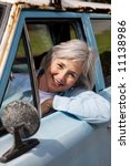 Smiling senior taking a cruise in the old rustbucket - stock photo