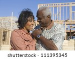 Small photo of Happy loving senior African American couple in front of incomplete house