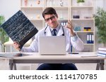 young doctor looking at x ray... | Shutterstock . vector #1114170785