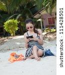 Asian Women play tablet on the Beach - stock photo
