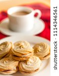 Small photo of Shortbread swirls filled with raspberry jam and creme filling with a hot drink in the background