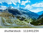 Summer Stelvio pass with alpine road and snow on slope (Italy) - stock photo