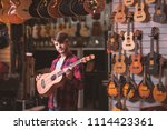 young musician with a guitar in ... | Shutterstock . vector #1114423361