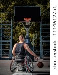 Small photo of Cripple basketball player in a wheelchair plays on open gaming ground.