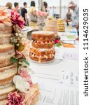 Small photo of Cakes decorated with flowers and fruit are lined up at a country fete and await judging. People linger in the distance examine the entries.