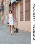 woman with a dog walking down... | Shutterstock . vector #1114640939