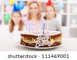 Home made happy birthday cake with the party girls in background - stock photo