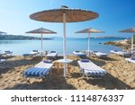 umbrellas with sunbeds on... | Shutterstock . vector #1114876337