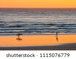distant surfers silhouettes on... | Shutterstock . vector #1115076779
