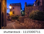 Small photo of Upper view down on evening street with street lights and houses, girl statue, bush, coarse stone walls and stairs all lit with lamp light under blue dusk sky in ancient town in Costa Brava (Spain)
