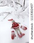 a toy rabbit walks in a snowy... | Shutterstock . vector #1115302457