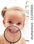Happy little girl with missing milk tooth showing the gap through magnifier - stock photo