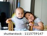 little sister hugging her baby... | Shutterstock . vector #1115759147