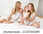 family females sitting on bed... | Shutterstock . vector #1115764289