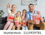 Small photo of cheerful family eating popcorn and watching tv together at home