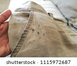 dirty shorts in hand. oil stain ... | Shutterstock . vector #1115972687