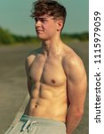 Young adult male standing shirtless outside on a warm summer's day - stock photo