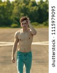 Young adult male walking forward shirtless while running a hand through his hair, on a warm summer's day - stock photo
