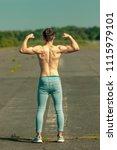 Young adult male flexing his muscles viewed from the back on a warm summer's day - stock photo