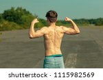 Young adult male flexing his back muscles on a warm summer's day - stock photo