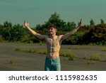 Young male adult with his arms out enjoying the sunshine shirtless on a warm summer's day - stock photo