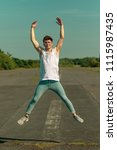 Young adult male jumping outside in the sunshine - stock photo