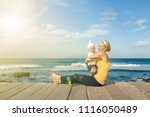 baby boy playing with mother on ... | Shutterstock . vector #1116050489