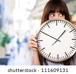 a young girl holding a clock ...