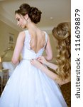 Small photo of Bridesmaid is lacing white wedding dress for beautiful bride. Beauty model girl in bridal gown for marriage. Female portrait. Woman with curly hair and lace veil. Cute lady indoors