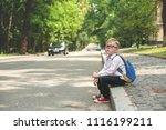 alone child sitting on the road.... | Shutterstock . vector #1116199211