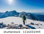 Small photo of A mountaineer walking on snow on a beautiful bright sunny day in the mountains. Adventure winter climb in alpine landscape. Alpinism in Kamnik Savinja alps, Slovenia.