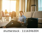 Stock photo handsome man working on his laptop in a hotel room 1116346304
