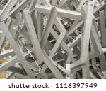 Small photo of Chaotic ligament galvanized steel structures angular profile. Close-up. Metal products in the industrial outdoors storage site. Industrial abstract background.