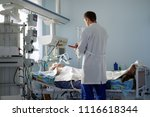 Small photo of intensive care caucasian doctor examines intubated critical stance patient writing notes to case report in intensive care department